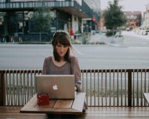 Vrouw is aan het freelance tekstschrijven op haar laptop op een terras.