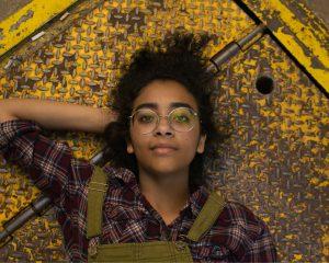 slim meisje, liggend op de grond. Ze draagt een bril, blouse en overall.