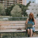 Vrouw op een bankje met haar laptop