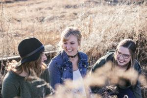 Drie vriendinnen die de grootste lol hebben en gieren van het lachen.