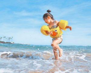 Speel jij weleens met de zeegolven? Het meisje met zwembandjes op de foto heeft er de grootste plezier in.