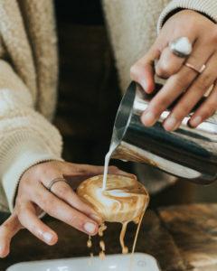 Kopje koffie waarbij melk over de rand komt