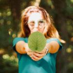 Vrouw met een blad in haar hand wat symbool staat voor een duurzame onderneming