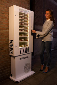 Girlboss Jessica van VINADA bij een ouderwetse snoepautomaat gevuld met flesjes VINADA.